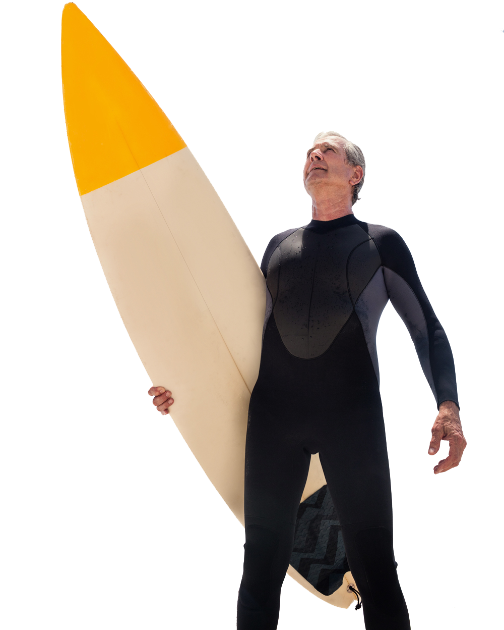 Image of a man over 50 in a black wetsuit holding a surfboard and looking at the sky