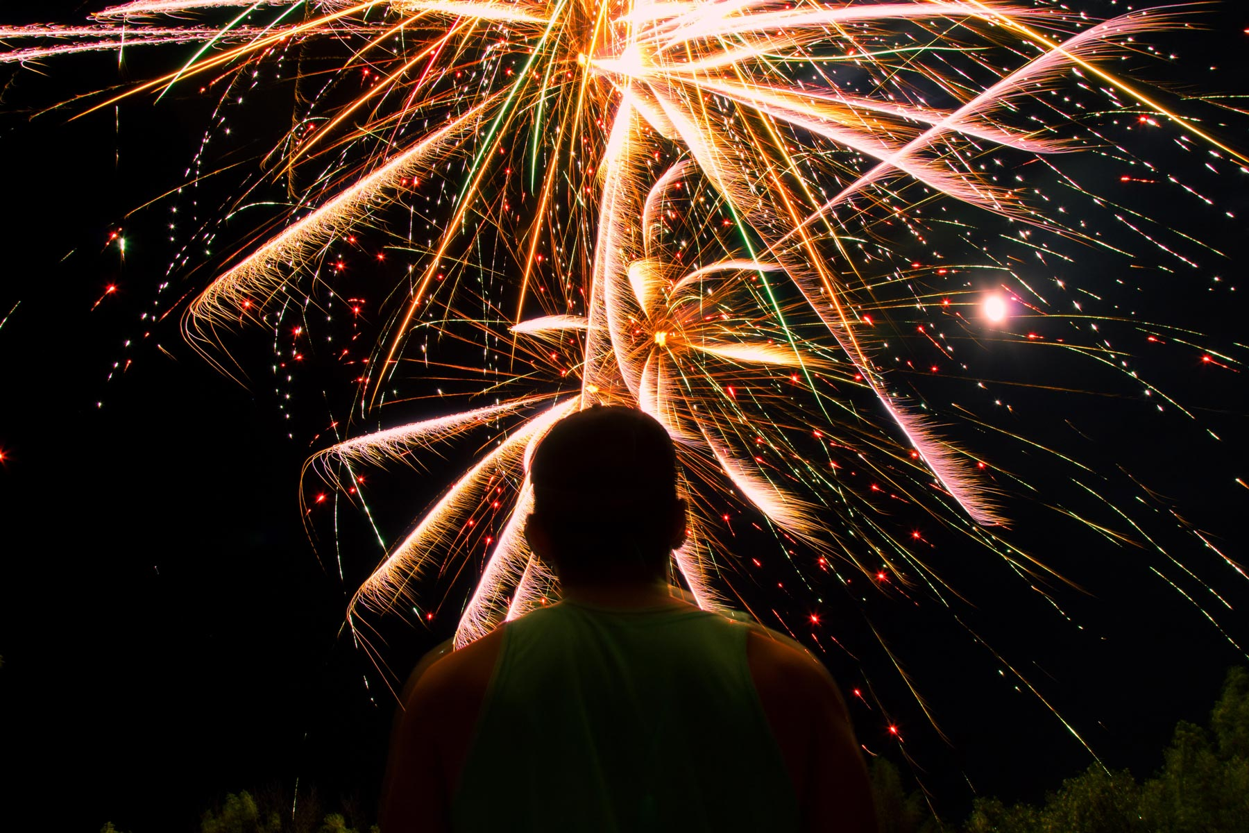 Image of a man looking up at fireworks in the night sky