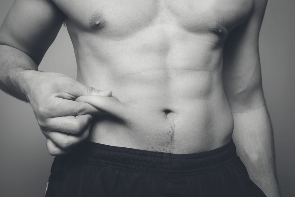 Image of a young man's muscular ab area while he pinches a roll of fat