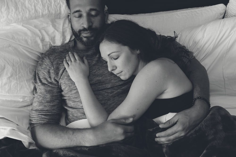 Black and white image of a couple laying together in bed with eyes closed symbolizing distress over sexual function problems